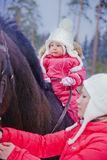 Baby girl horseback riding stock images