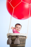Baby girl on hot air balloon in the sky Stock Photos