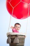 Baby girl on hot air balloon in the sky Stock Photos