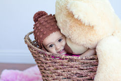 Baby girl hugging big teddy bear in basket. A cute 11 month old baby girl, wearing a knitted hat, gives a giant teddy bear a big hug. Both baby and teddy bear royalty free stock photography