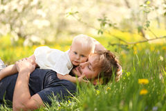 Baby Girl Hugging Father in Flower Meadow Stock Images