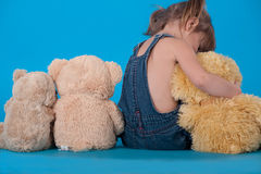 Baby girl hugging with her toys Stock Photos