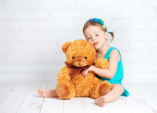 Baby girl hugging a loved teddy bear Stock Photo