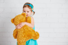 Baby girl hugging a loved teddy bear Royalty Free Stock Images