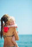 Baby girl hugging mother on beach Royalty Free Stock Photos