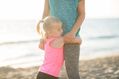Baby girl hugging mother on beach in the evening Royalty Free Stock Photo