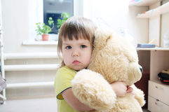 Baby girl hugging teddy bear indoor in her room, devotion concep. T, big bear toy royalty free stock photo