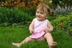 Baby-girl iin a pink dress. Happy little baby-girl iin a pink dress on the grass Royalty Free Stock Photo