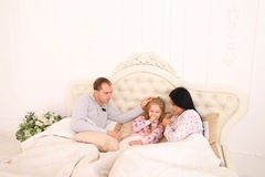 Baby girl ill, mother wipes snot on bed. Women caring for sick child, wiping nose with tissue. Child in bed with mom and dad. Young couple caring of their Stock Images