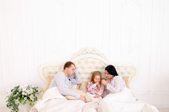 Baby girl ill, mother wipes snot on bed. Women caring for sick child, wiping nose with tissue. Child in bed with mom and dad. Young couple caring of their Stock Photos