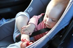 Baby in a car seat playing with her toes royalty free stock photography