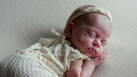 Baby girl infant in dress asleep. In the crib Stock Image