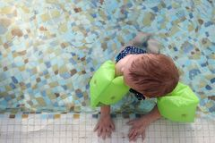 Baby girl with inflatable armbands. Child learning to swim in pool royalty free stock image
