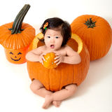 Baby girl inside the pumpkin Royalty Free Stock Photos