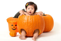 Baby girl inside the pumpkin Stock Photos