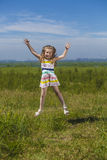 Baby girl jumping on a meadow Royalty Free Stock Image