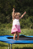Baby girl jumping on trampoline Royalty Free Stock Photo