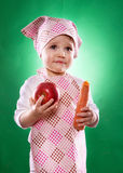The baby girl with a kerchief and kitchen apron holding an vegetable isolated Stock Photography