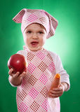 The baby girl with a kerchief and kitchen apron holding an vegetable isolated Royalty Free Stock Photos