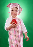 The baby girl with a kerchief and kitchen apron holding an vegetable isolated Stock Image