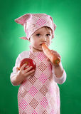 The baby girl with a kerchief and kitchen apron holding an vegetable isolated Royalty Free Stock Image