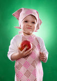 The baby girl with a kerchief and kitchen apron holding an vegetable isolated Stock Photos