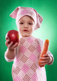 The baby girl with a kerchief and kitchen apron holding an vegetable isolated Royalty Free Stock Images