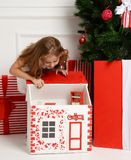 Baby Girl Kid playing with christmas red house in play room at home or kindergarten with little dolls toys Stock Photography