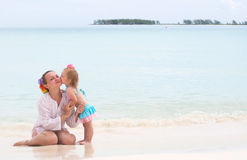 A baby girl is kissing her mother on the beach Royalty Free Stock Photo
