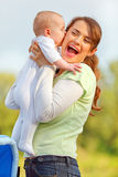 Baby girl kissing holding her happy mother Stock Images
