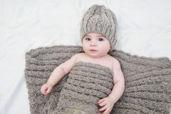 Baby girl in knitted hat. And mittens on a bed royalty free stock image