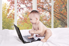 Baby girl with laptop on bedroom Stock Image