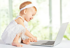 Baby girl at  laptop computer. Baby girl at a laptop computer Royalty Free Stock Photography