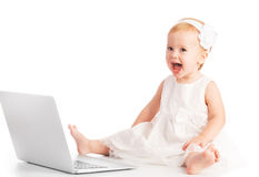 Baby girl at laptop computer. Baby girl at a laptop computer isolated stock photos