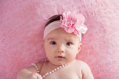 Baby Girl with a Large, Pink, Flower Headband and Pearls Stock Photo