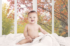 Baby girl laughing on the bedroom Stock Photos