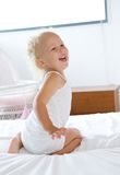 Baby girl laughing and playing in bed Stock Photo
