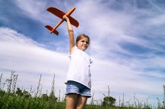 A baby girl is launching a toy airframe glider in a field against a blue sky background with clouds. Stock Image