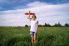 A baby girl is launching a toy airframe glider in a field against a blue sky background with clouds. Royalty Free Stock Images