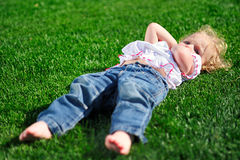 Baby girl laying on the green grass in the park Stock Photos