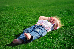 Baby girl laying on the green grass in the park royalty free stock image
