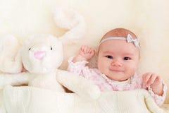 Baby girl laying on her blanket with her stuffed bunny Stock Photo