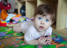 Baby girl laying on her tummy. Little caucasian girl laying on the mat among her toys. Her eyes are blue and looks big. She looks surprised Stock Photos