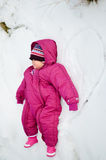 Baby girl laying in snow. Cute child laying in snow.  dressed with warmer Stock Photo