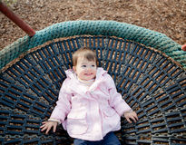 Baby girl laying on a swing smiling Stock Photos