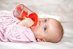 Baby girl laying witn baby bottle Royalty Free Stock Photo