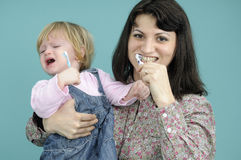 Baby girl learning brushing teeth. White child studying brushing tooth and mother teaching Stock Images