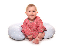 Baby girl learning to sit using a pillow. Cutout Stock Images