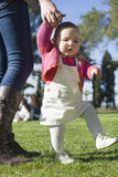 Baby girl learning to walk at grass park Stock Photo