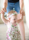 Baby girl learning to walk. With her mother helping Royalty Free Stock Photo